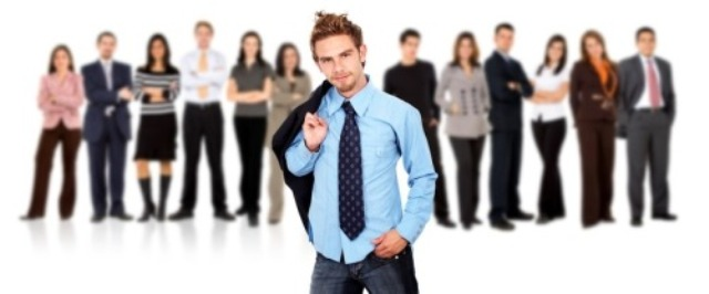 Business team standing over a white background with a young entrepreneur standing out from the crowd in front